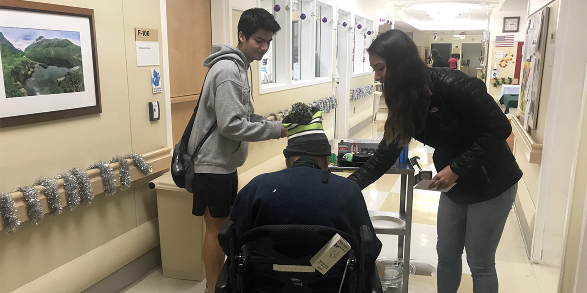 members of United Students for Veterans Health in a hallway with a veteran in a wheelchair
