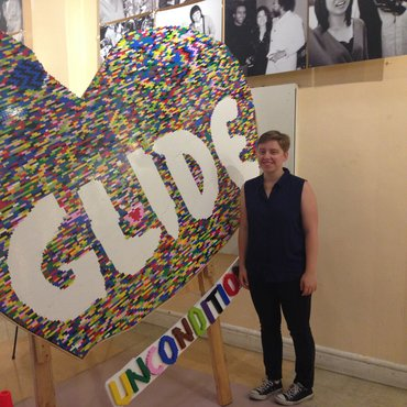 "Erica McDowell stands next to a large heart with ""GLIDE"""